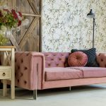 różowa tapicerowna sofa z metalowymi nogami