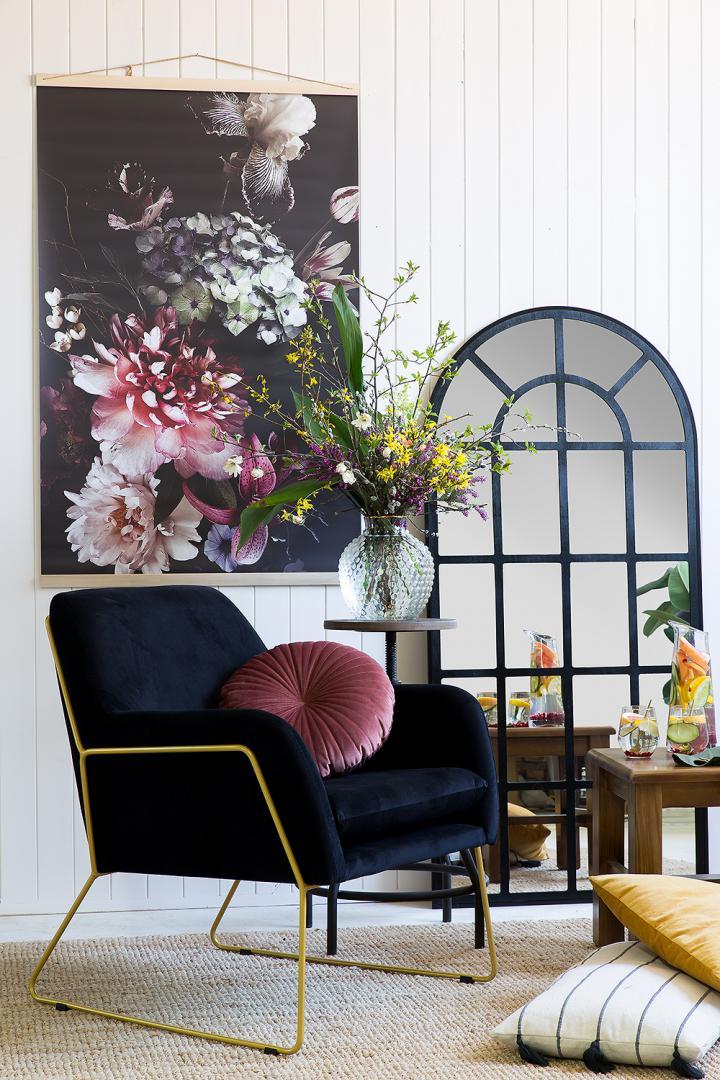 ciemnogranatowy tapicerowany fotel z metalowymi złotymi nogami